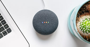 google home sobre mesa blanca y laptop mac